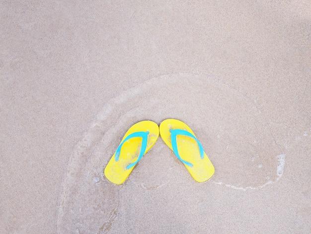 Sandália amarela no fundo bege da praia do verão da areia.