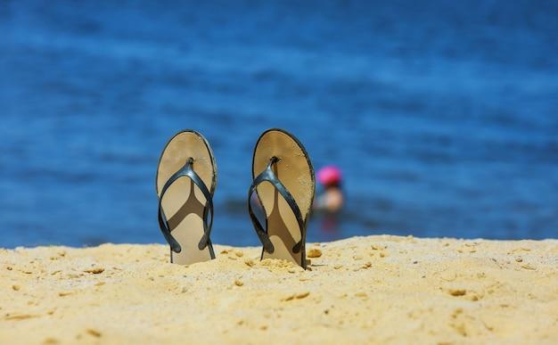 Sandália flip flop na praia de areia branca com fundo azul do oceano em férias