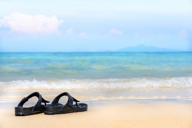 Sandália flip flop na praia de areia com mar azul do oceano