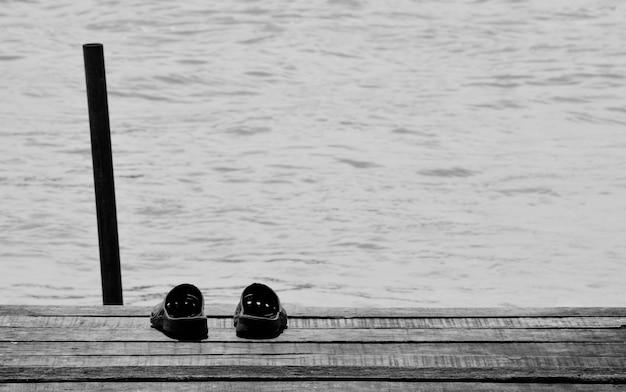 Sandália no antigo porto de madeira no mar