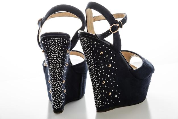 Sandálias azuis femininas elegantes com salto alto e tachas em um espaço em branco.