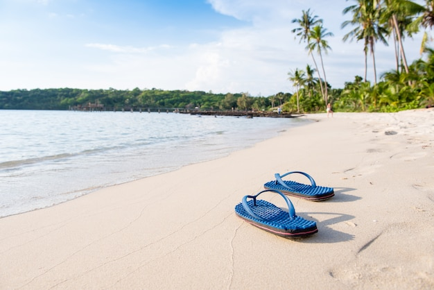 Sandálias azuis na praia com o pôr do sol ou nascer do sol