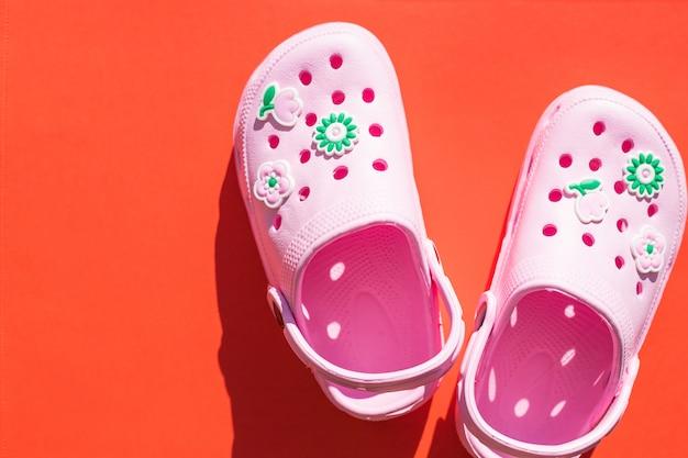 Sandálias cor-de-rosa isoladas. sapatas de borracha em um fundo vermelho.