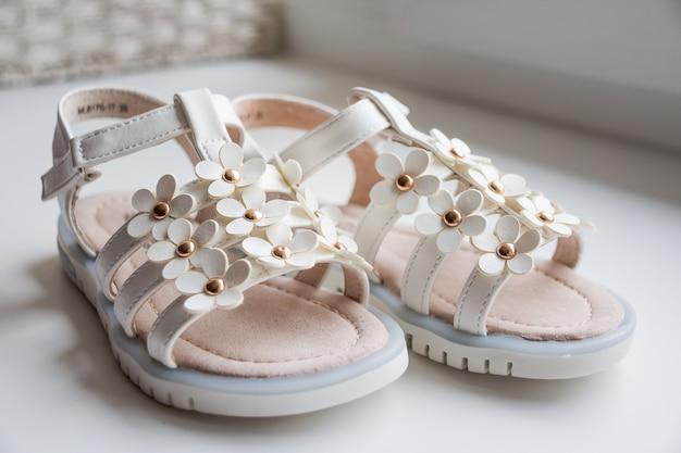 Sandálias de bebê menina em fundo branco