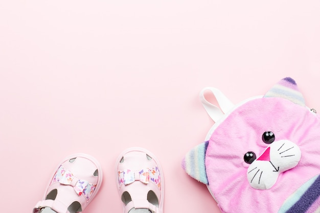 Sandálias de bebê, mochila em fundo pastel.