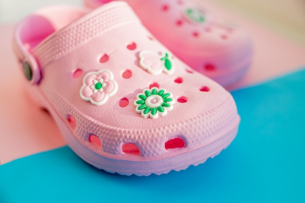 Sandálias de borracha das crianças coloridas isoladas no fundo azul.