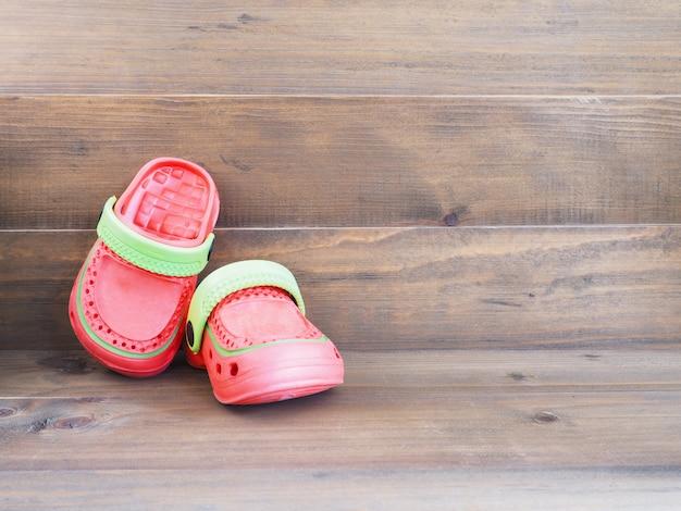 Sandálias de borracha infantil em fundo de madeira