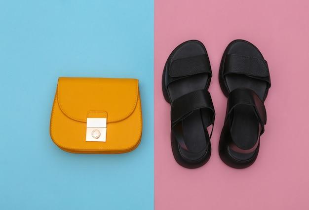 Sandálias de couro e uma bolsa amarela em um fundo rosa azul. vista do topo. postura plana