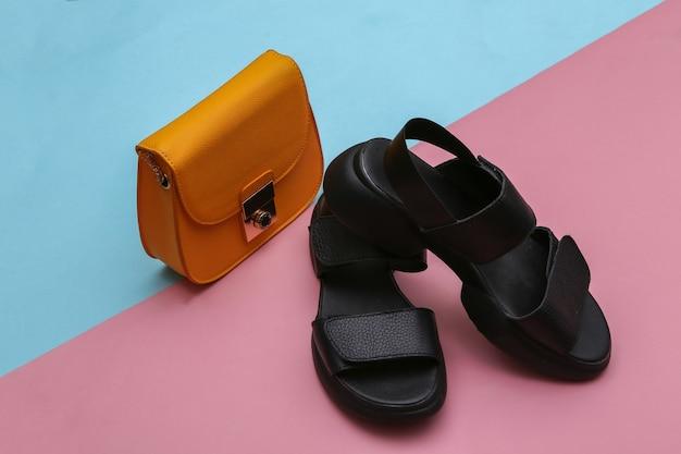 Sandálias de couro e uma bolsa amarela em um fundo rosa azul.