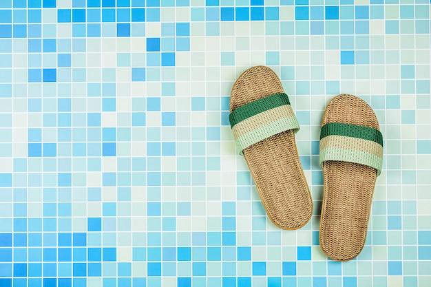 Sandálias em azulejos azuis na piscina. - conceito de férias de verão.