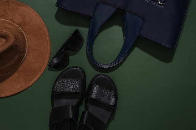 Sandálias femininas, chapéu, bolsa e óculos de sol sobre fundo verde. acessórios femininos. vista do topo