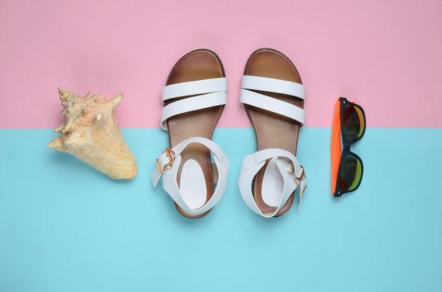 Sandálias femininas de couro na moda, conchas, óculos de sol em uma superfície colorida pastel, vista superior, plana leigos