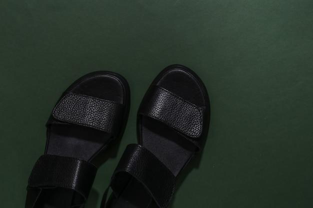Sandálias femininas de couro preto sobre fundo verde. vista do topo