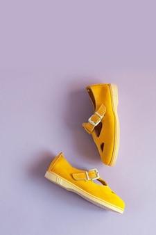 Sandálias femininas de verão amarelo em fundo lilás com espaço de cópia. foto vertical. vista de cima.