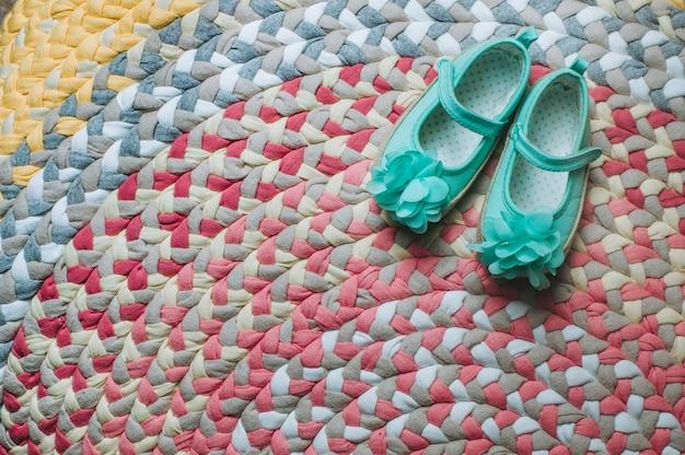 Sandálias infantis no tapete colorido feito à mão
