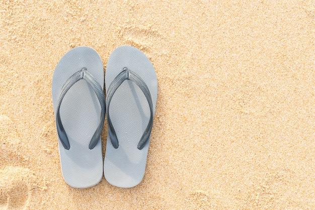Sandálias na costa do mar arenoso