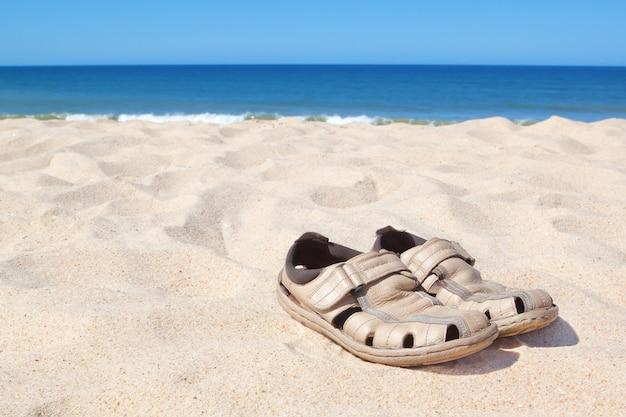 Sandálias na praia perto do mar.