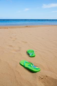 Sandálias verdes deixadas no caminho para a água na praia arenosa
