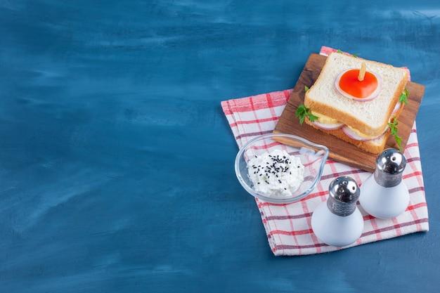Sanduíche a bordo ao lado de sal e uma tigela de queijo no pano de prato no azul.