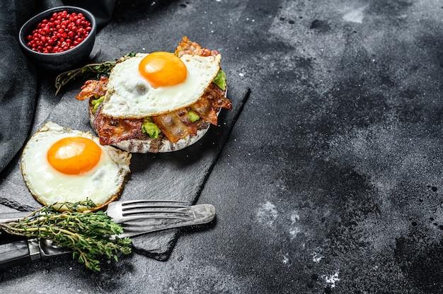 Sanduíche aberto com abacate, bacon frito e ovo. fundo preto. vista do topo. copie o espaço.