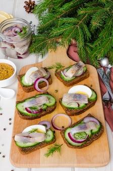Sanduíche aberto com pão de centeio, pepino fresco, cebola em conserva, arenque e endro. aperitivo para o ano novo e o natal.