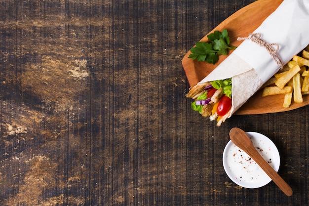 Sanduíche árabe de kebab plano de madeira