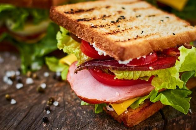 Sanduíche caseiro com presunto, alface, queijo e tomate em um fundo de madeira