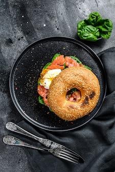Sanduíche caseiro de pãozinho com salmão, creme de queijo, espinafre e ovo. superfície preta. vista do topo