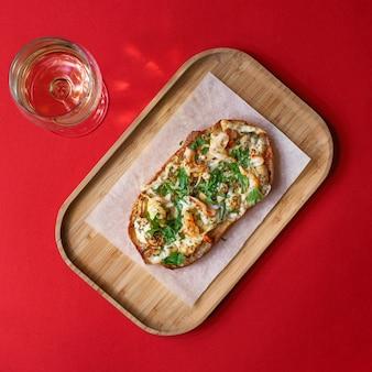 Sanduíche caseiro delicioso com camarão cozido e cogumelos com queijo. vidro de vinho branco, vista superior, parede vermelha. alimentação saudável para toda a família