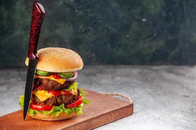 Sanduíche caseiro saboroso e garfo na tábua de madeira no lado direito na superfície desfocada