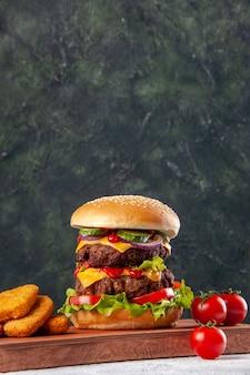 Sanduíche caseiro saboroso e tomates nuggets de frango tomates na tábua de madeira na superfície borrada