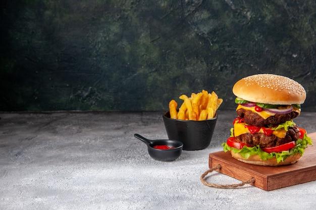 Sanduíche caseiro saboroso na tábua de madeira com tomates e batatas fritas no lado esquerdo na superfície desfocada