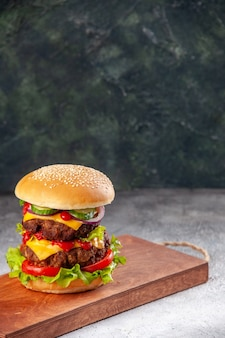 Sanduíche caseiro saboroso na tábua de madeira na superfície desfocada