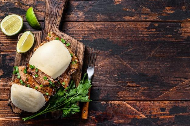 Sanduíche chinês cozido no vapor, pãezinhos de gua bao com carne de porco. fundo preto. vista do topo. copie o espaço.