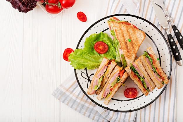 Sanduíche club - panini com presunto, queijo, tomate e ervas. vista do topo