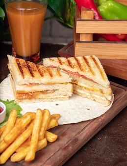 Sanduíche club servido com batata frita e refrigerante, maionese, ketchup
