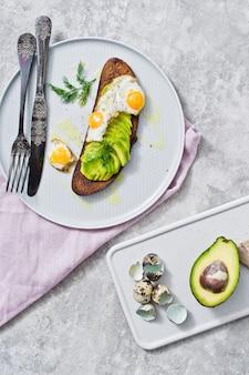Sanduíche com abacate e ovo no brinde do pão preto.