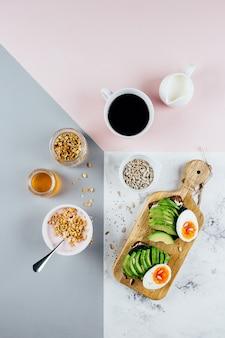 Sanduíche com abacate e ovos cozidos, iogurte com granola, xícara de café sobre fundo tricolor