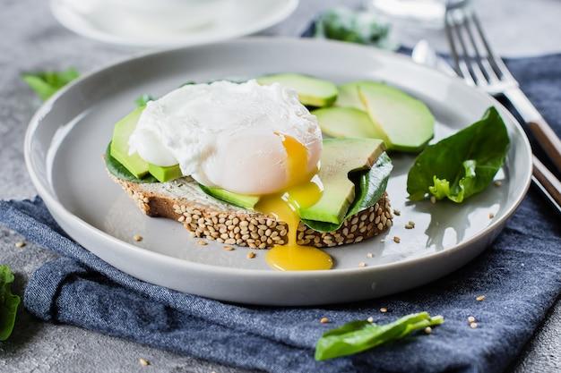Sanduíche com abacate, espinafre e ovo escalfado no pão integral na chapa de pedra fundo