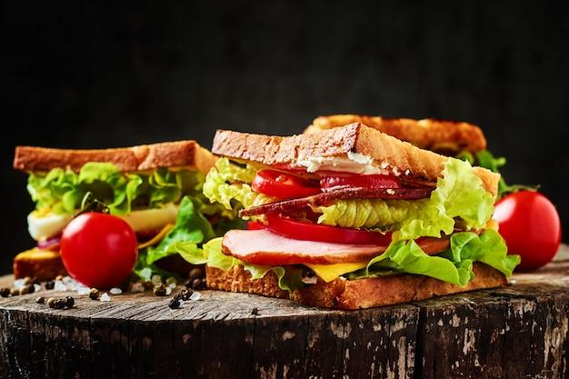 Sanduíche com alface, presunto, tomate e cebola em um escuro close-up