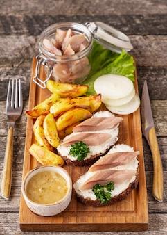 Sanduíche com arenque na placa de madeira.