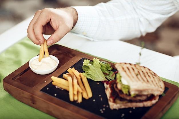 Sanduíche com bacon frito e batatas fritas