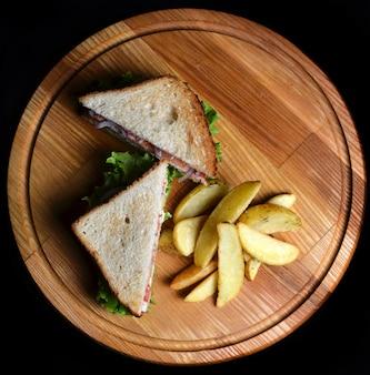 Sanduíche com batatas fritas em uma placa de madeira isolada em um fundo preto. vista do topo. comida restaurada. comida rápida.