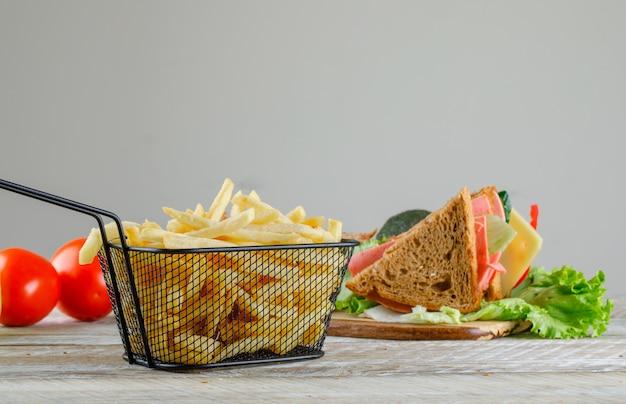 Sanduíche com batatas fritas, vista lateral de tomates na mesa de madeira e cinza