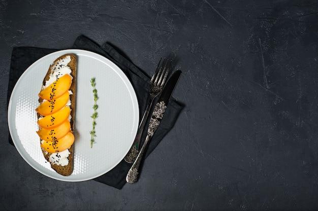 Sanduíche com caqui e queijo macio com copyspace.