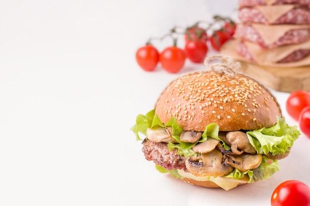 Sanduíche com carne e cogumelos ao lado dos ingredientes. fechar-se. tem espaço de cópia