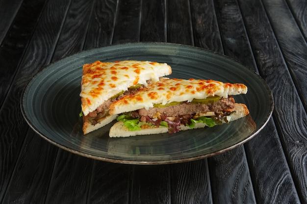 Sanduíche com carne, pepino em conserva, salada e queijo derretido
