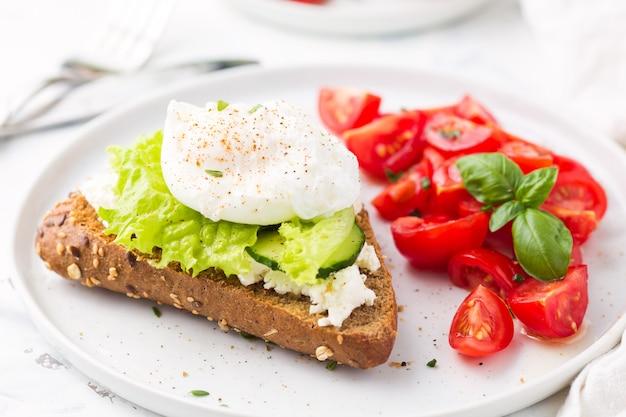 Sanduíche com creme de queijo, salada e ovo escalfado.