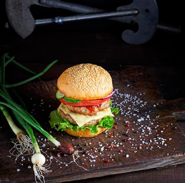 Sanduíche com duas costeletas de carne, queijo e legumes