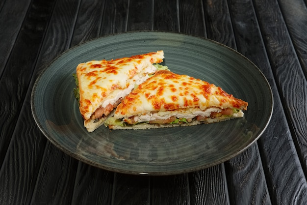 Sanduíche com filé de frango, pepino em conserva, salada e queijo derretido